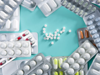 blisters of medical pills over greenbackground as a pharmaceutical industry concept